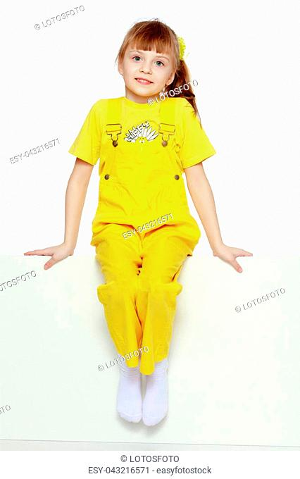 Girl with a short bangs on her head and bright yellow overalls.She crouched down on the white advertising banner