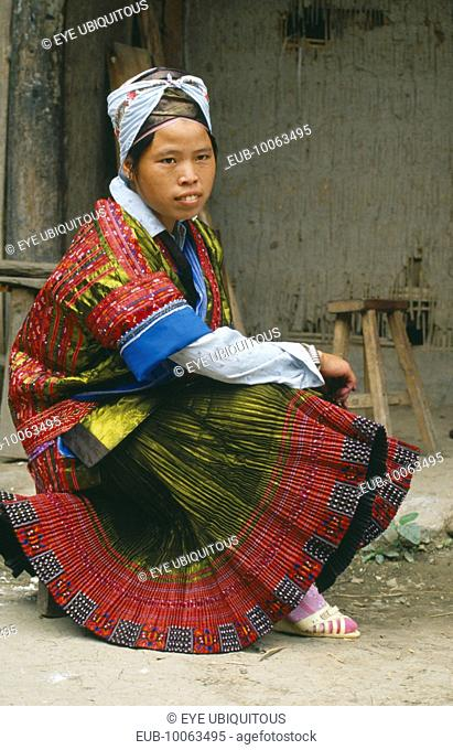 Seated Miao girl in festival dress