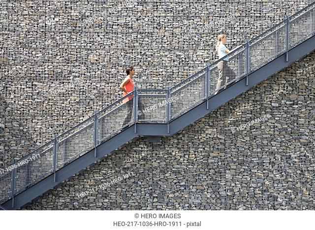 Side view of businesswomen climbing staircase