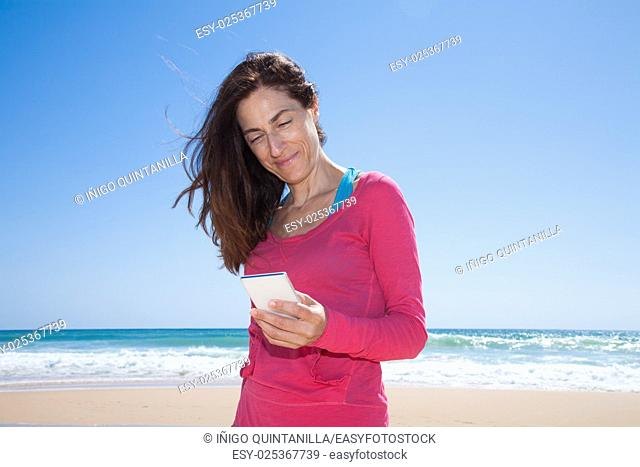 portrait of brunette woman with pink sweater smiling and touching mobile phone smartphone at beach with sea and blue sky behind