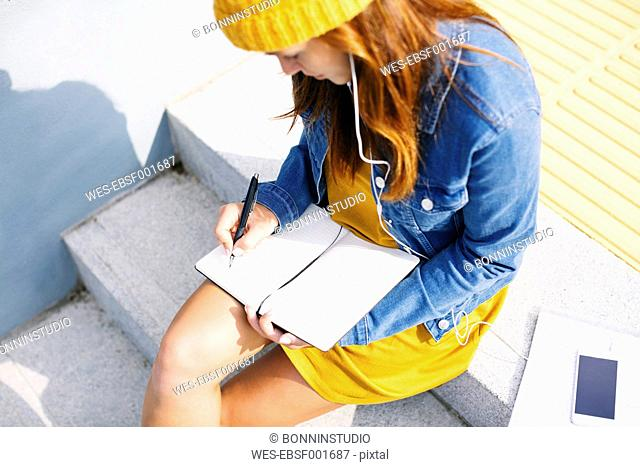 Young woman sitting on steps writing down something