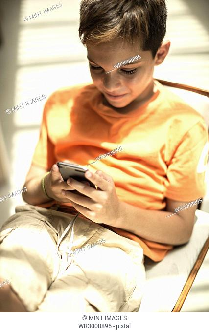 A boy sitting looking at a mobile phone screen