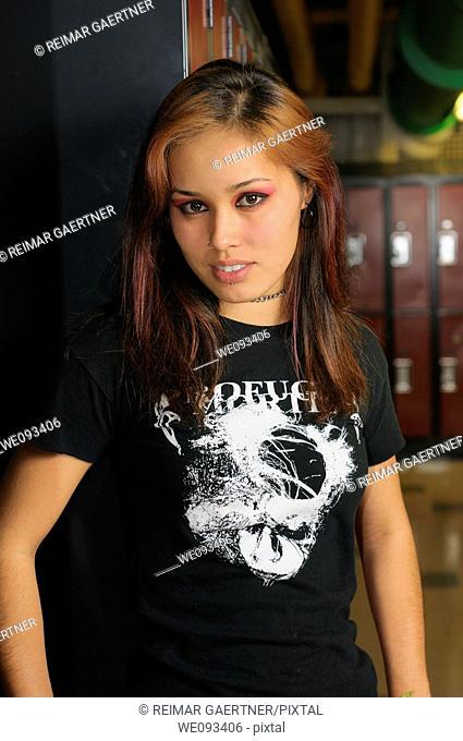 Pretty young female metal punk rocker student in a basement school locker room