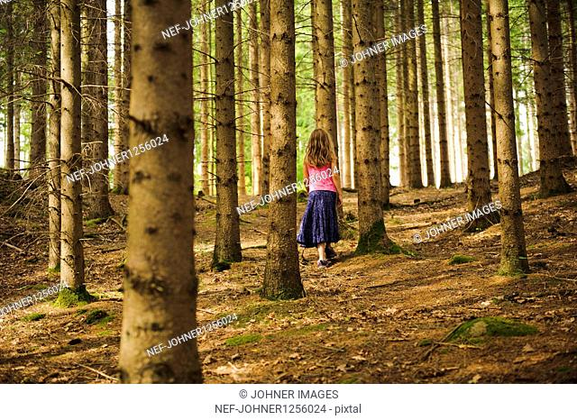 Girl walking among trees in forest