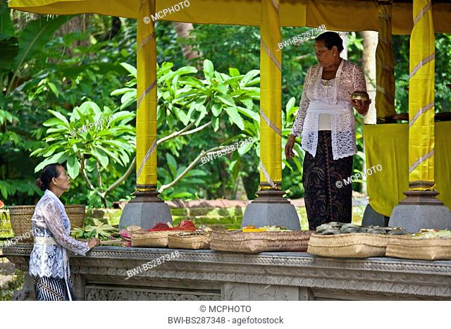 two women and baskets with offerings at the Pura Taman Sarawati temple, Indonesia, Bali, Ubud