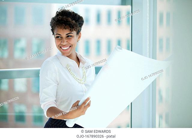 Businesswoman reading blueprints in office
