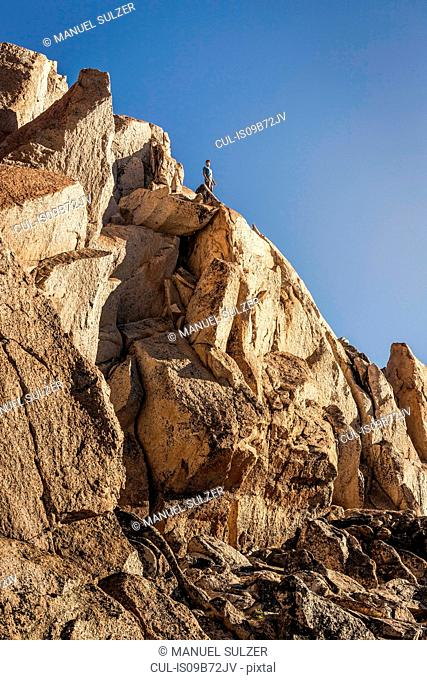Male mountaineer looking out from top of rugged rock face, Andes, Nahuel Huapi National Park, Rio Negro, Argentina