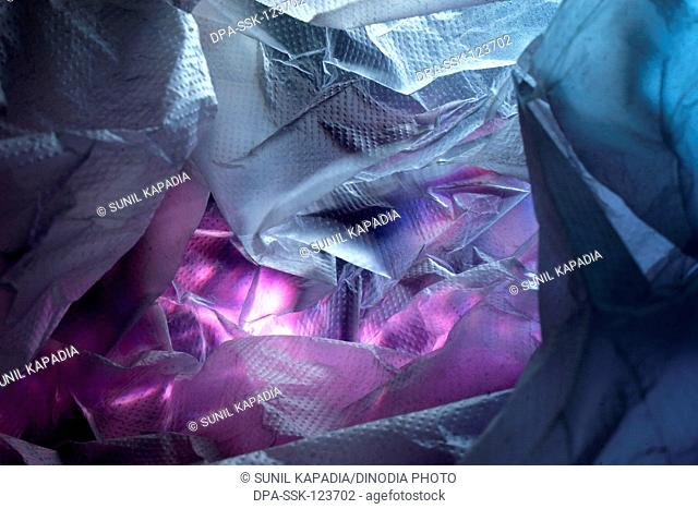 Abstract of  plastic shopping bag on pink gift wrapping paper in blue and red light ; Pune ; Maharashtra ; India