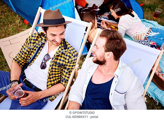 Friends sitting in deck chairs in music festival