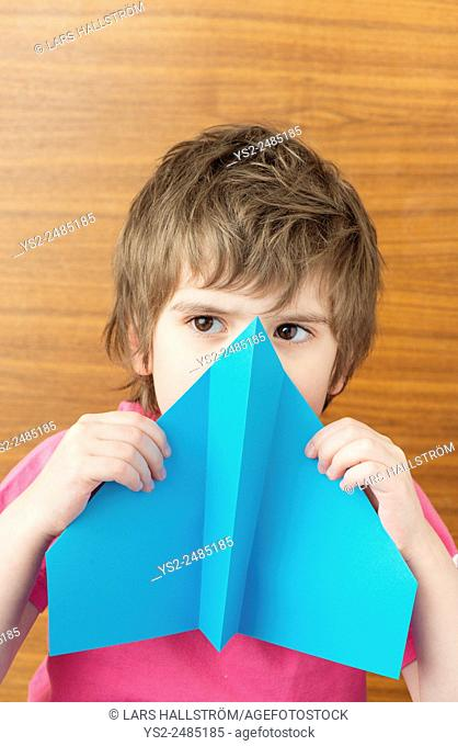 Young child holding blue paper airplane in front of face