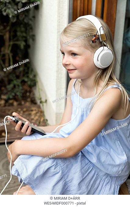 Smiling little girl listening music with headphones and smartphone