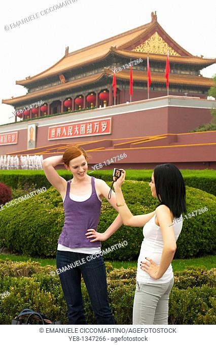 Tourists, one taking photos of the other, in front of The Gate of Heavenly Peace, The Forbidden City, Beijing, China, Asia  MR
