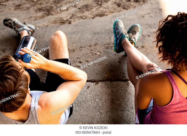 Overhead view of joggers taking break on kerb