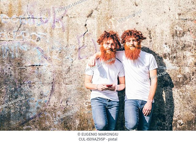 Portrait of young male hipster twins with red beards standing in front of wall
