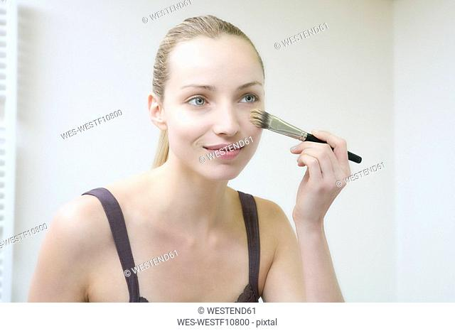 Young woman using make-up brush, portrait