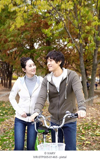 Young Couple In A Park In Autumn With Bicycle