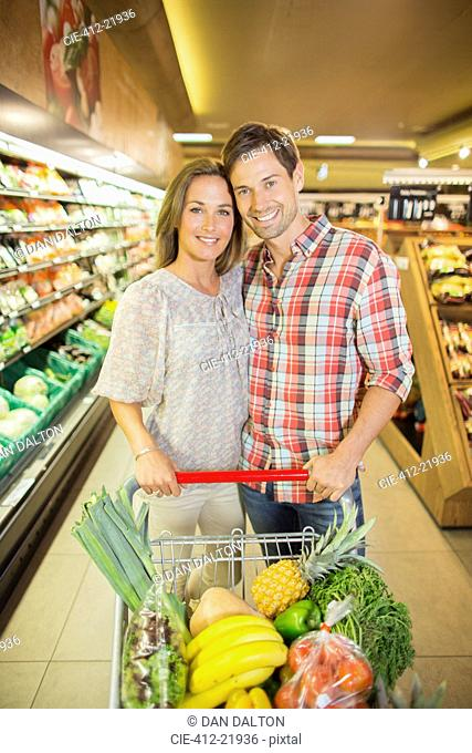 Couple pushing full shopping cart in grocery store