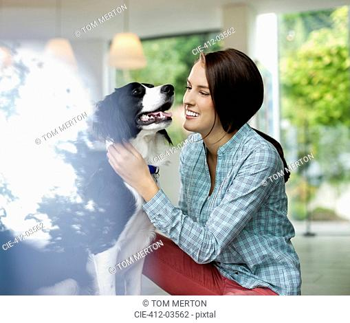 Smiling woman petting dog indoors