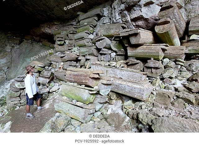 a male tourist looks at over 100 old wooden coffins that are stacked at the entrance to the lumiang burial cave near the mountain village of sagada