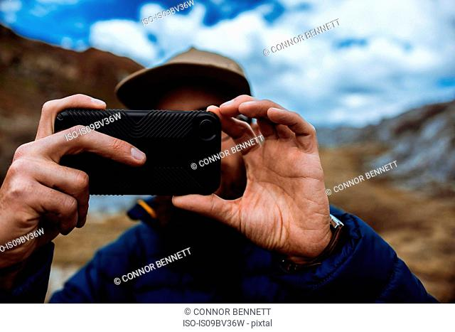 Hiker taking picture with phone, Mineral King, California, United States