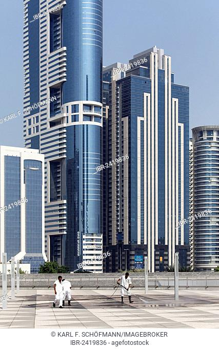 Workers cleaning a terrace in front of skyscrapers with a high pressure washer, Sheikh Zayed Road, Dubai, United Arab Emirates, Middle East, Asia