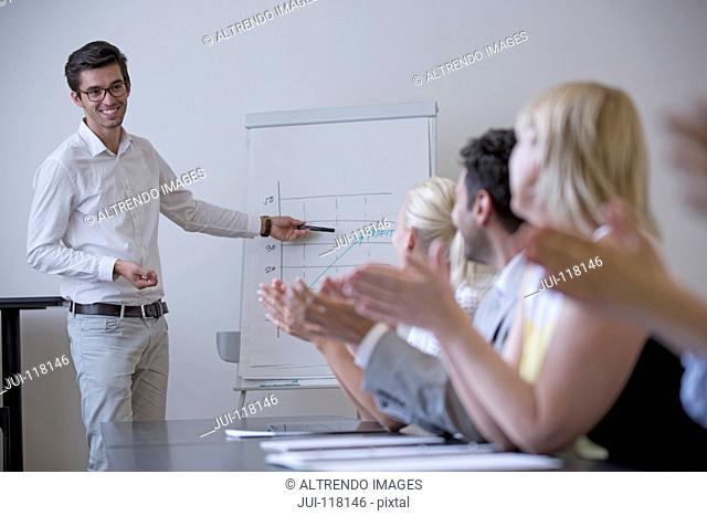 Businessman Stands At Flipchart Giving Presentation