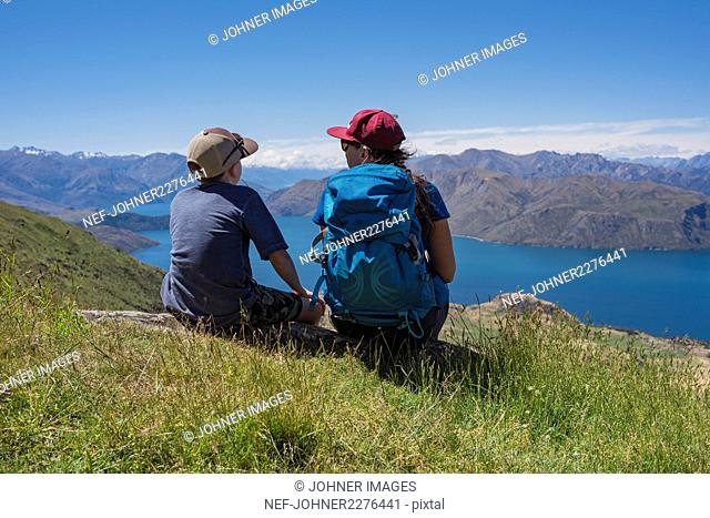 Boy with woman looking at lake in mountains