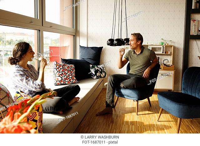 Couple drinking wine while sitting on window seat and chair at home