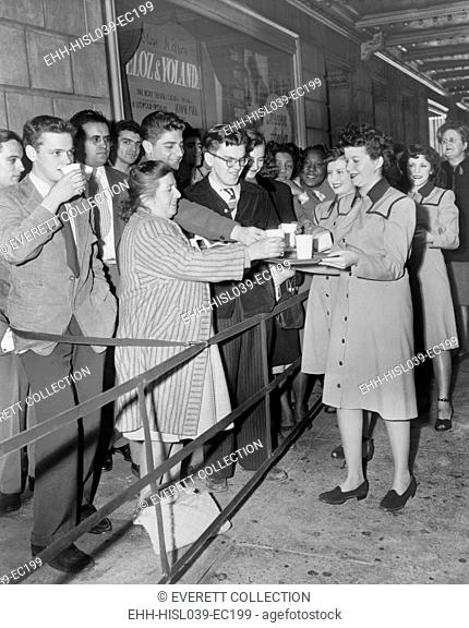 Roxy Theater usherettes dispense coffee and doughnuts to movie patrons at the premiere of 'Forever Amber'. New York City, 1947. - (BSLOC-2014-17-127)