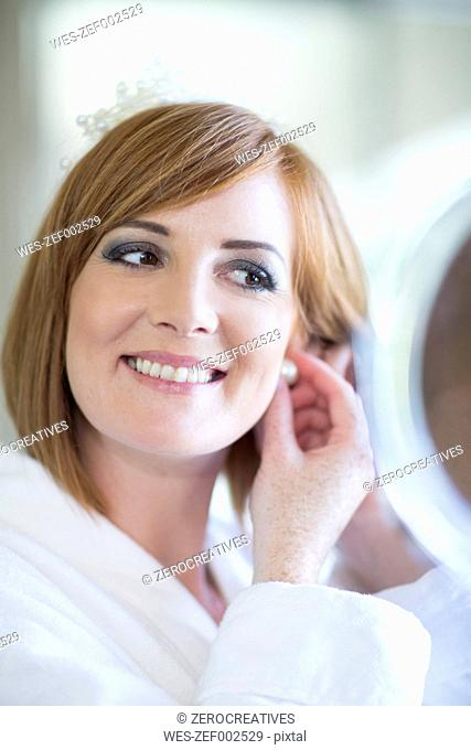 Smiling young woman putting on earrings