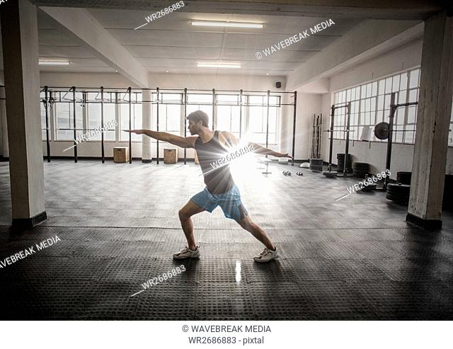 Man stretching in gym with flare