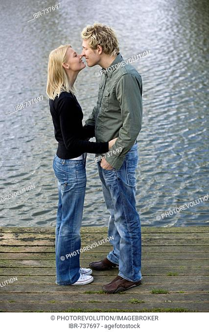Couple touching noses on a wooden dock
