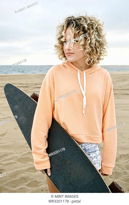 Young woman with curly blond hair wearing pink hoodie standing on sandy beach, holding skateboard