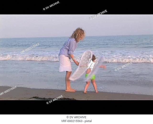 Medium shot of a mom and daughter playing on the beach