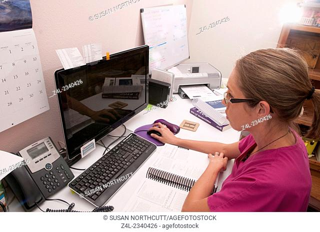 a medical professional is sitting at her desk working on her computer
