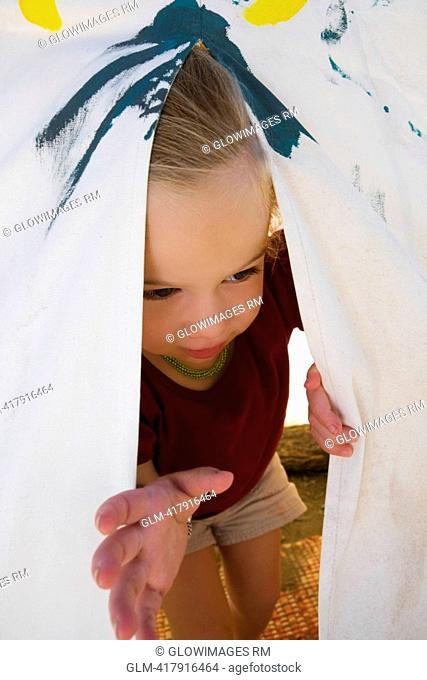 Baby girl peeking out from a tent