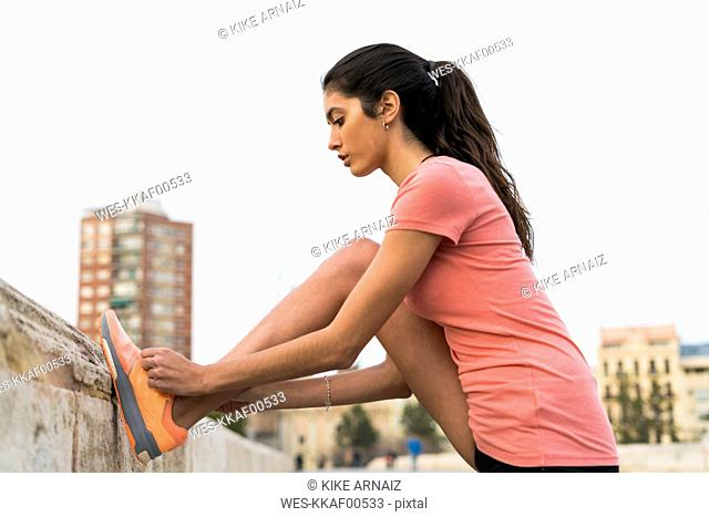 Young woman lacing her shoes before running