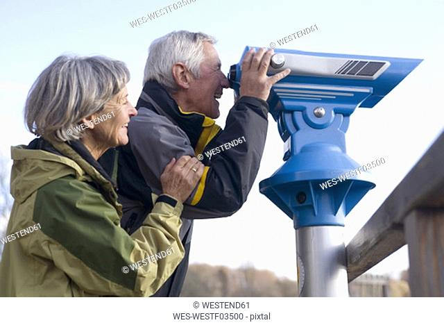 Senior couple, man looking through telescope, side view