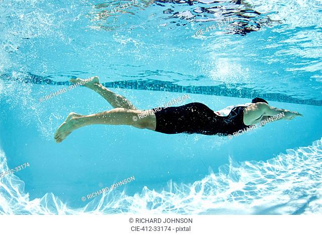 Male swimmer athlete swimming underwater in swimming pool