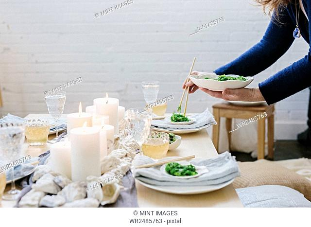 A woman placing a plate of food on a table decorated with lighted candles