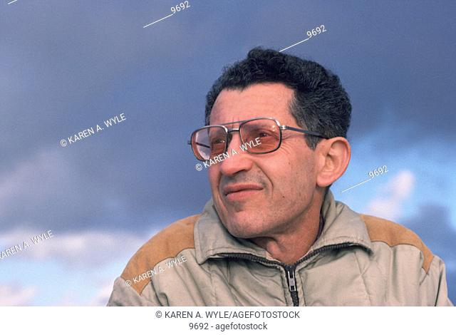 Older dark-haired man outdoors in warm jacket looking off into distance against dramatically cloudy sky