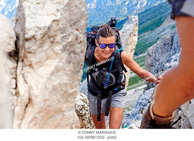 Woman hiking up mountain smiling, Austria