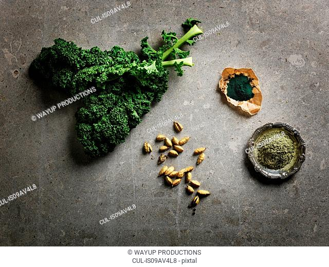 Overhead view of leafy vegetables, cardamom pods and ground supplements