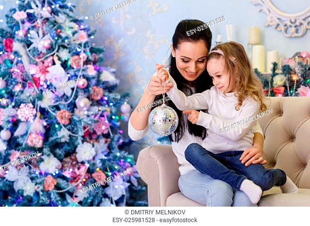 The pretty girl with mum sitting near Christmas tree in the house. Happy family. Merry Christmas and New Year