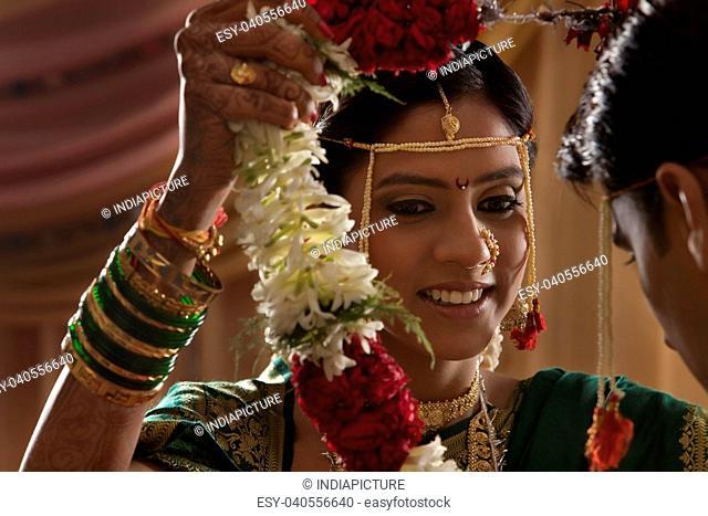 Maharashtrian bride and groom exchanging garlands in wedding