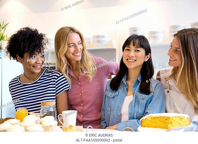 Young women smiling together in cafe