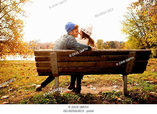 Rear view of romantic young couple on park bench at lakeside
