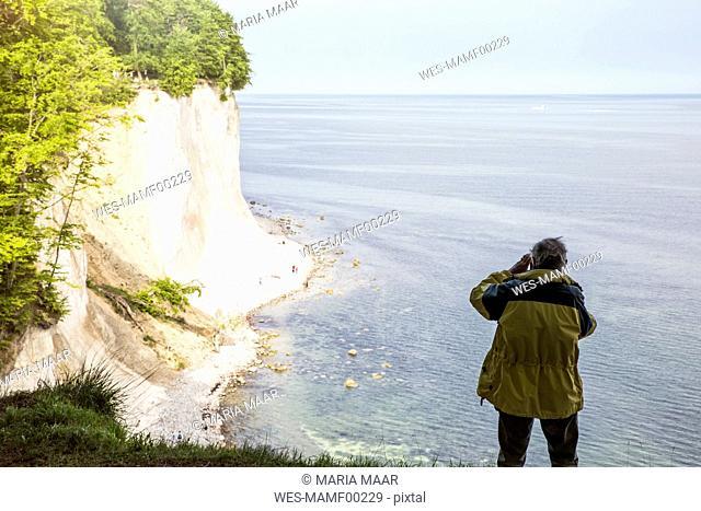 Germany, Mecklenburg-Western Pomerania, Ruegen, Jasmund National Park, chalk cliff, hiker photographing on viewpoint