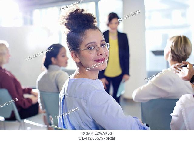 Portrait smiling, confident businesswoman turning, looking back in conference audience