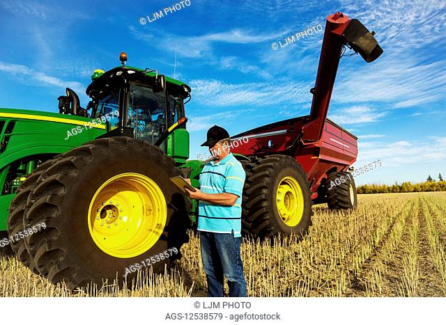 Farmer standing in a canola field beside a tractor with a wagon and using a tablet to assess his yield from the harvest on a warm fall evening; Edmonton